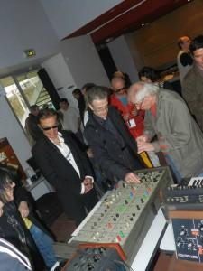 Rimbert e Geiss assistem demonstração de um synth vintage.