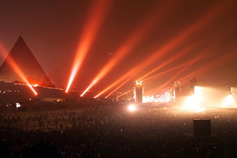 "GIZA, EGYPT: Laser projectors light the sky of the Giza pyramids as Egypt ushers in its eighth millennium early 01 January 2000 with an ultra-modern ""cyberconcert"" conducted by French multi-media wizard Jean-Michel Jarre. As the rest of the world marked the beginning of the year 2000, the age-old monuments were spotlit by lasers that bounced off them into the surrounding desert to the sound of techno music. (Photo credit should read MARWAN NAAMANI/AFP/Getty Images)"